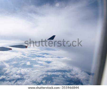 View of beautiful sunny clouds and wing of airplane from Window. Travel, Transportation and Tourism background. Business, Holidays and Vacations publications. Freedom concept - stock photo