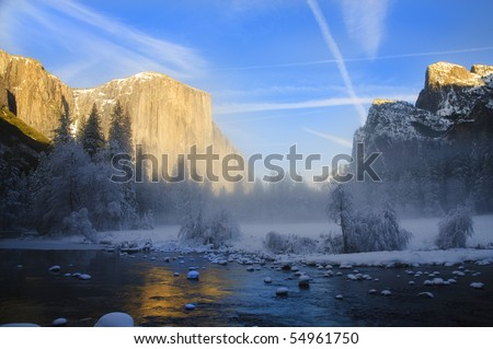 View of beautiful Yosemite valley in winter with the Merced river and snow covered El Capitan at sunset - stock photo