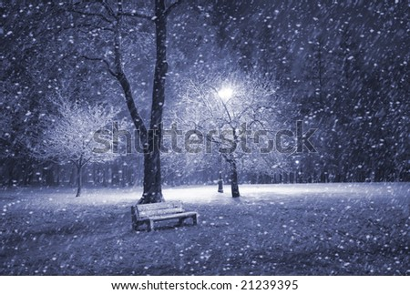 View of bench and shining lantern through snowing. Blue tone. Snow at night shot.
