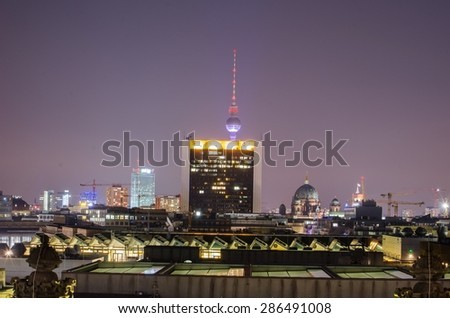 view of berlin skyline taken from the terrace of reichstag during night. fernsehturm is hidden behind a shopping center.