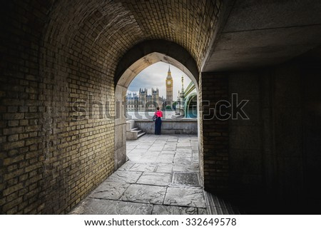 View of Big Ben and lady in red,  through the pedestrian tunnel at sunset, London. - stock photo