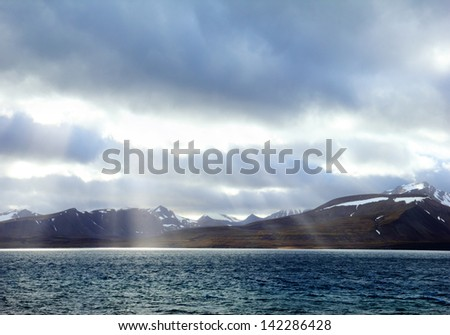 View of Black rocks with snow and dark water against the background of dramatic sky with bright shafts struck through the cloud near Barentsburg, Norway, Spitsbergen (Svalbard island), Greenland sea - stock photo