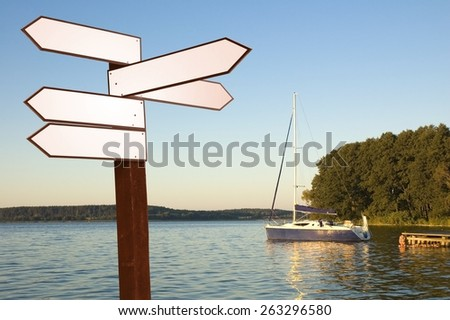 View of blank wooden multi-direction guidepost on a lakeshore, Mazury, Poland - stock photo
