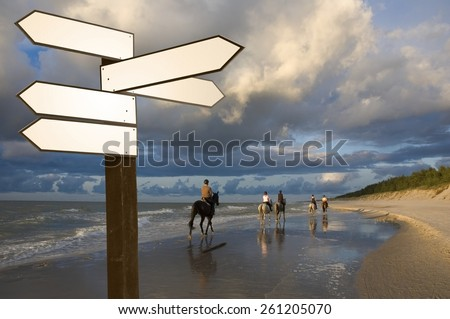 View of blank wooden multi-direction guidepost with horse riders on the Baltic Sea coast just before sunset, Poland - stock photo
