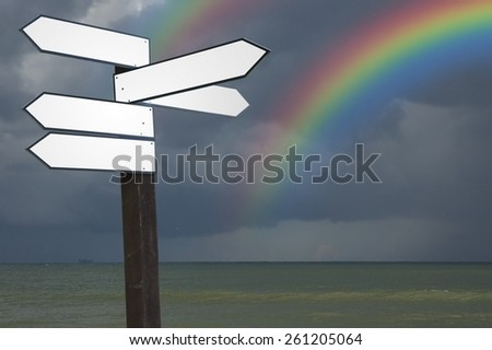 View of blank wooden multi-direction guidepost with rainbow on dark stormy sky over Baltic Sea water, Poland - stock photo