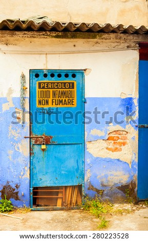 View of blue iron door with dangerous sign - stock photo