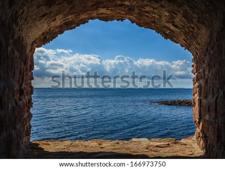 View of blue sea and sky from hole in old stonewall wall. Seascape in stone window casing frame. Travel tourism. - stock photo