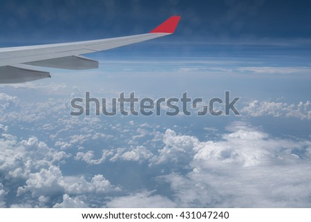 View of blue sky and clouds from airplane window, flying over Vietnam. Blue sky background and cloud view from window of the airplane. Beautiful background of airplane wing with blue sky and clouds. - stock photo