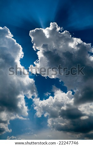 View of blue sky with sun rays through the clouds - stock photo