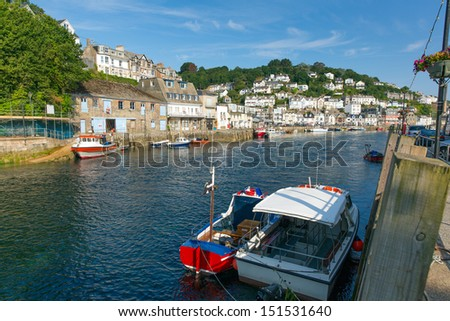 View of boats on Looe river Cornwall England, with blue sea on a sunny summer day and town on the hillside - stock photo
