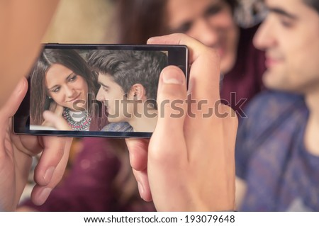 View of boy hands taking photos with a smartphone to hipster teenage couple sitting in the sofa. Focus on phone screen. - stock photo