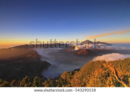 View of Bromo during sunrise from the top with a carpet cloud. Image has grain or blurry or noise and soft focus when view at full resolution. (Shallow DOF, slightly blur because of the carpet clouds)