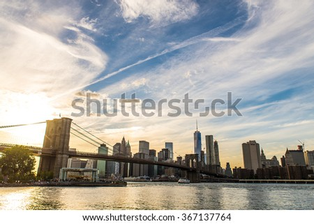 View of Brooklyn Bridge and Manhattan skyline at sunset - stock photo