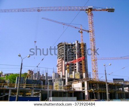 View of building of a complex of high-rises with construction cranes, against the blue sky. - stock photo