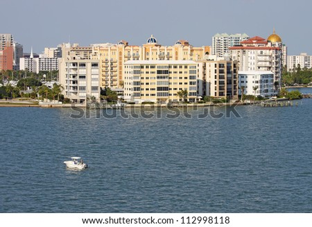 View of buildings on the edge of  Sarasota Bay, Sarasota, Florida from the water with a small pleasure boat, palm trees and blue sky. - stock photo