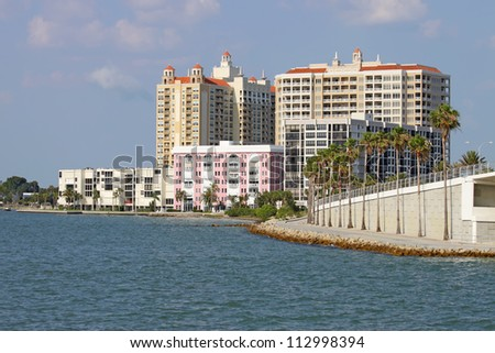 View of buildings on the edge of  Sarasota Bay, Sarasota, Florida from the water with palm trees, blue sky and clouds. - stock photo