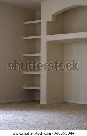 View of built in shelving units in modern vacant apartment living room. - stock photo