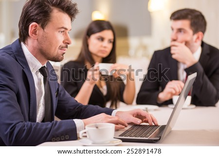 View of business meeting during coffee time. Focus on young man is working on laptop. - stock photo