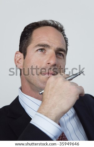View of businessman thinking and holding a pen with his hand on his chin.