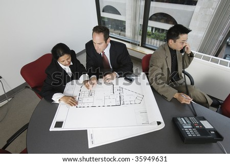 View of businesspeople checking blueprint with an architect speaking on phone.