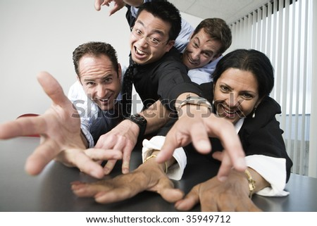 View of businesspeople reaching across a table. - stock photo