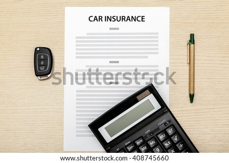 View of car keys and pen and calculator laying on a blank of insurance. - stock photo