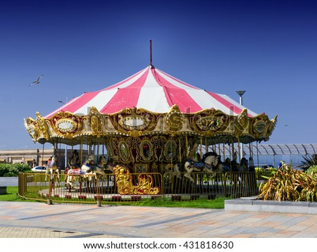 View of carousel on summers day; traditional merry-go-round under a brilliant summer sky  - stock photo