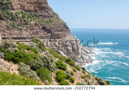 View of Chapmans Peak drive in the Table Mountain National Park in Cape Town, South Africa. Safety nets to keep rockfalls away from the road are visible  - stock photo