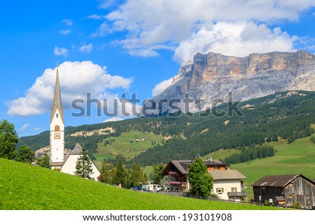 View of church in La Villa village on sunny summer day with mountains in the background, Trentino Alto Adige, Italy  - stock photo