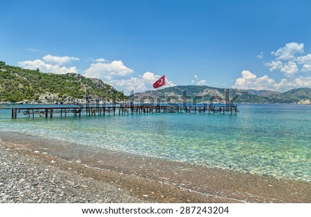 view of clear, transparent Aegean sea bay, green mountains and old pier with Turkish flag from pebble beach in Amos, Turkey - stock photo
