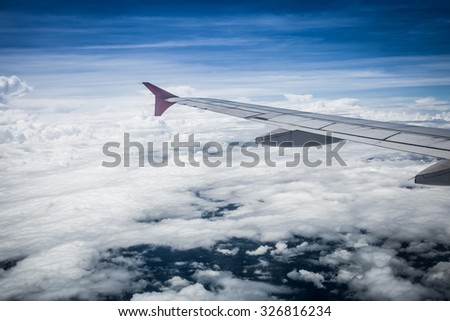 View of cloud sky and wing of airplane from window - stock photo