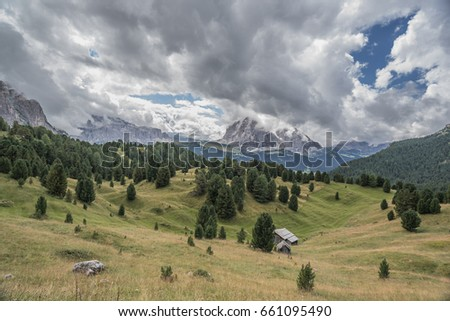 View of clouded Sassolungo with Sassopiatto mountain and Sella mountain group  as seen from hiking trail on Col Raiser plateau above St. Cristina village, Gardena valley, Dolomites, South Tyrol, Itlay