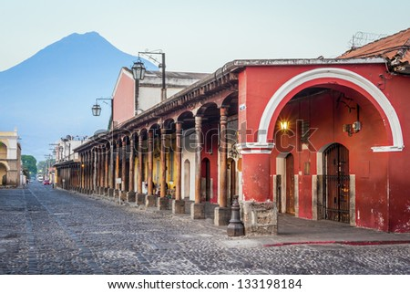 View of colonial buildings in Antigua central park with view of 'Agua' volcano in background - stock photo