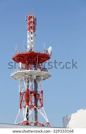 View of communications tower against blue sky - stock photo