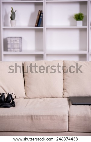 View of couch, laptop and headphone in room. - stock photo
