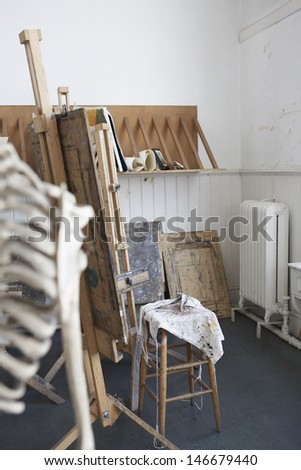 View of cropped skeleton and easel in artist's studio - stock photo