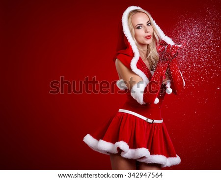 view of cute blond Santa girl blowing snowflakes from hand isolated on red background, celebration of Christmas time holidays - stock photo