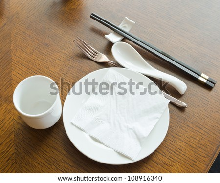 view of dinner place setting. A white plate with stainless fork and cup and chopsticks on the  wood table - stock photo