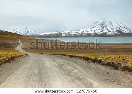 View of dirt road and Miscanti lagoon in Sico Pass, Chile - stock photo