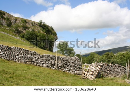 View of dry stone wall and broken gate in field in Yorkshire Dales - stock photo