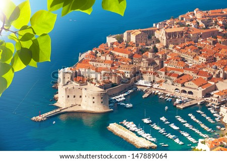 View of Dubrovnik old town port from the mountain above through the foliage - stock photo