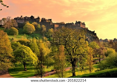 View of Edinburgh Castle and Princes Street Gardens at sunset - stock photo