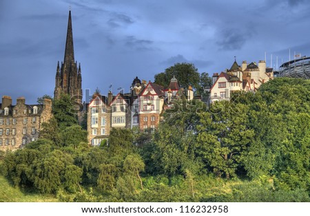 View of Edinburgh old city with the tower of the Parish Church of Saint Cuthbert above the trees of Princes Street Gardens