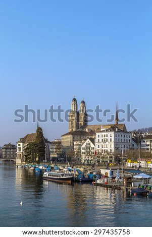 view of embankment of Limmat river with Grossmunster church, Zurich, Switzerland - stock photo