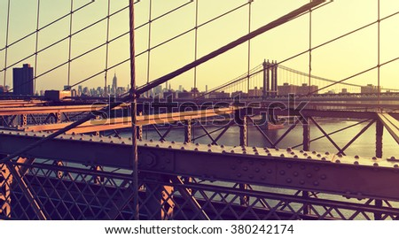 View of Empire State Building, Manhattan Bridge and Hazy City Skyline Through Support Cables and Past Girders of Historic Brooklyn Bridge at Warm Sunset, New York City, New York, USA - stock photo