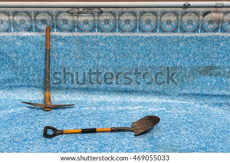 View of empty, in-ground swimming pool, with pick and shovel.