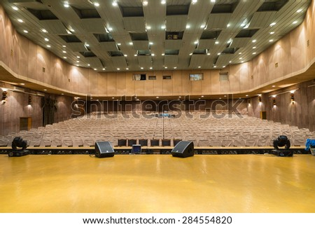 View of Empty Seats with Seat Covers Looking Toward Back of Theater from Empty Stage in Well Lit Venue - stock photo