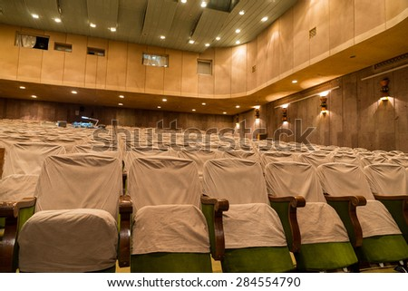View of Empty Seats with Seat Covers Looking Toward Back of Theater in Well Lit Venue