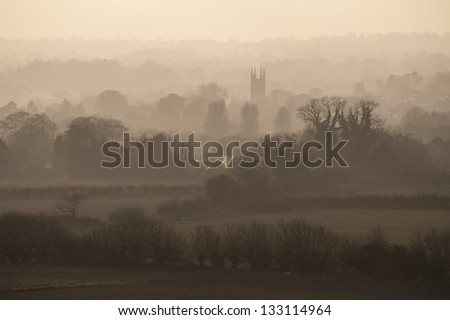 View of English countryside in the mist with a village and its church at the center of the scene - stock photo