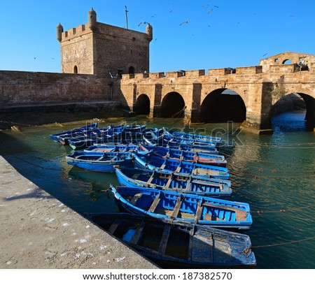 View of Essaouira port with blue fishing boats and the fortress of Castelo Real of Mogador, Morocco, the Atlantic coast, North Africa - stock photo
